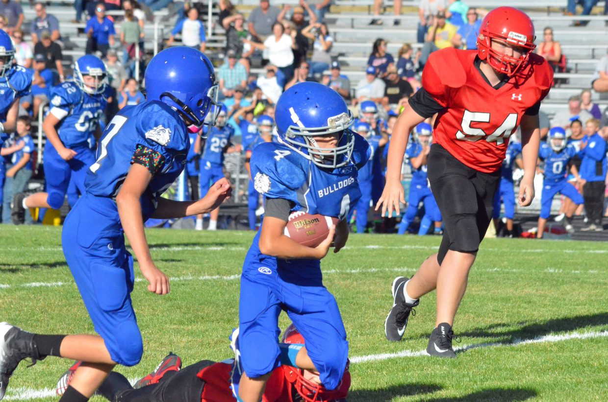 Craig Middle's School's Noah Duran tucks away the ball to run back and interception against Steamboat Springs.