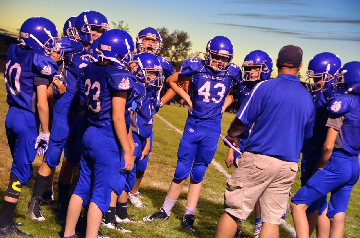 Craig Middle's School football players convene with coach Dusty Vaughn during a timeout against Steamboat Springs.