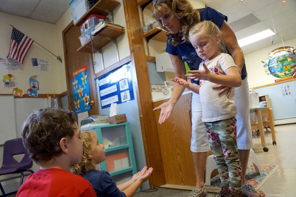 Glitter is used to demonstrate how germs are spread. Angie Roberts directs Hazel Billig to touch hands with Ava Myers and Jase Schnackenberg.