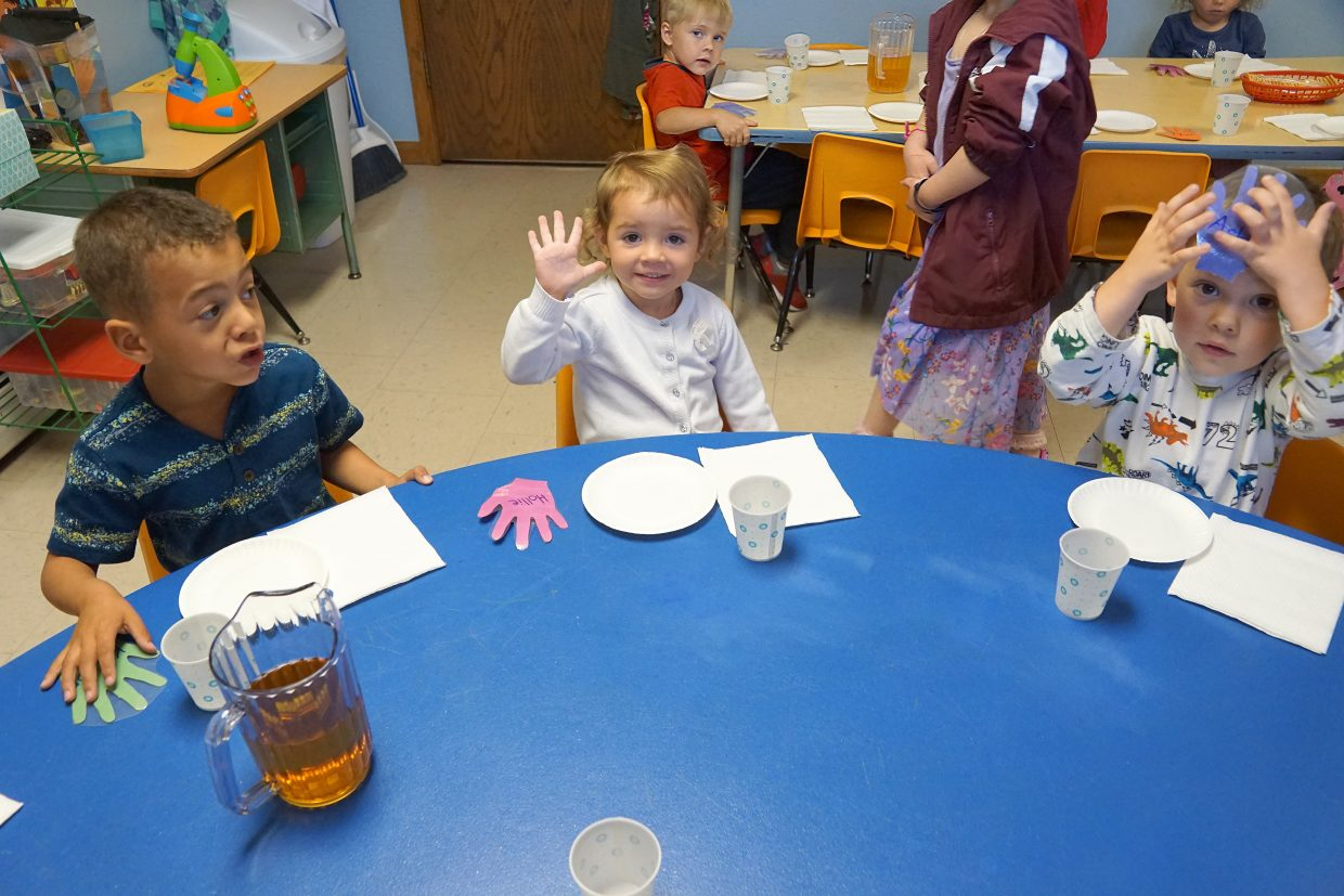 Showing freshly scrubbed hands Kason Weber, left, Hollie Mannon and Asher Willey sit down for family style snack time when children learn table manners and how to use their words to ask for items.
