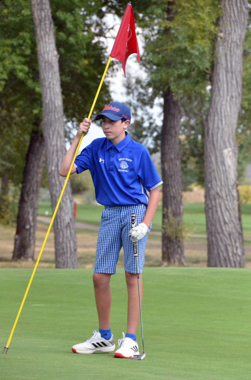 Moffat County High School's Tanner Etzler tends a pin Wednesday at Yampa Valley Golf Course during the MCHS Invitational.