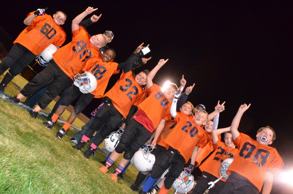 The players and coaches with Big O Tires Broncos celebrate their win of the championship game Wednesday night for Doak Walker fifth- and sixth-grade tackle football.