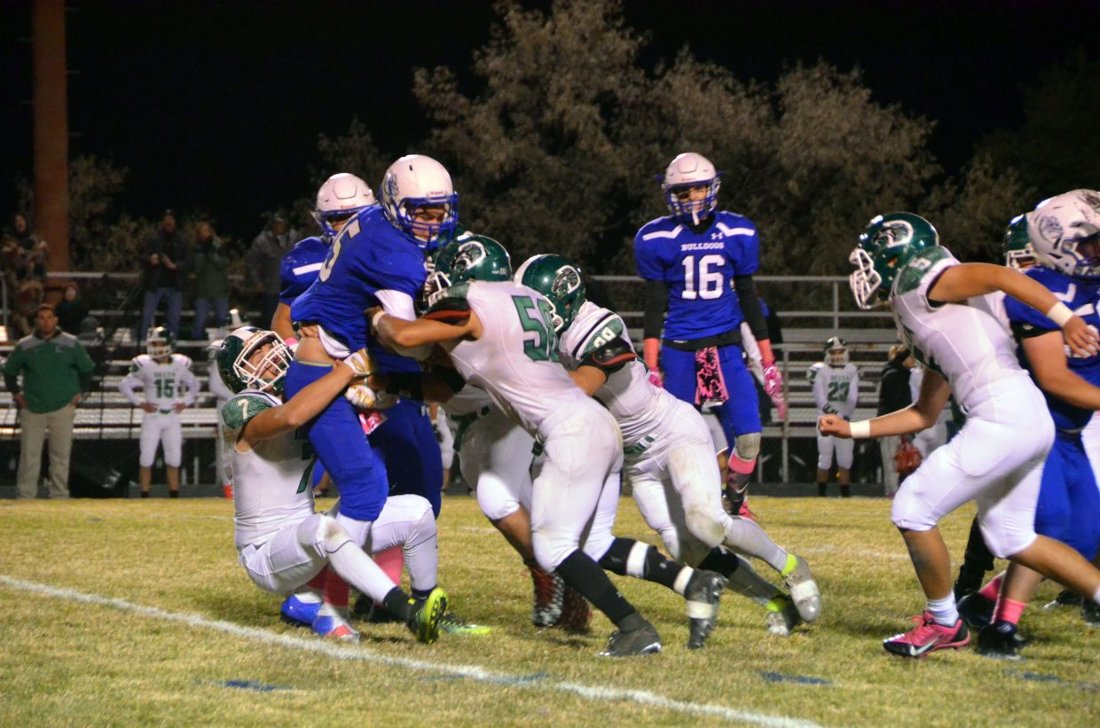 Delta defenders pile up on Moffat County High School's Colby Beaver.