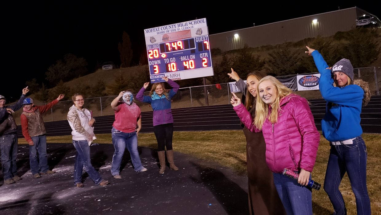 The Moffat County High School student section motions to the scoreboard at halftime as Bulldogs lead  Delta.