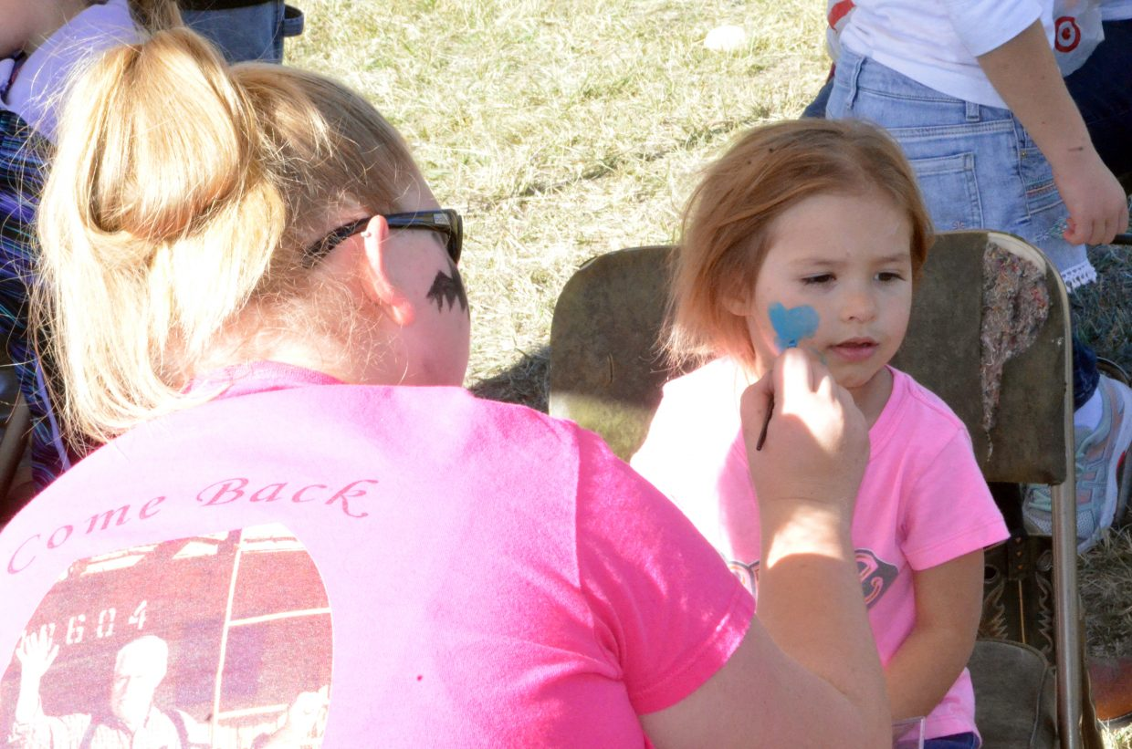 McKenzie Farmer, 4, gets a butterfly on her cheek at the face-painting booth during Saturday's pumpkin patch at Wyman Living History Museum.