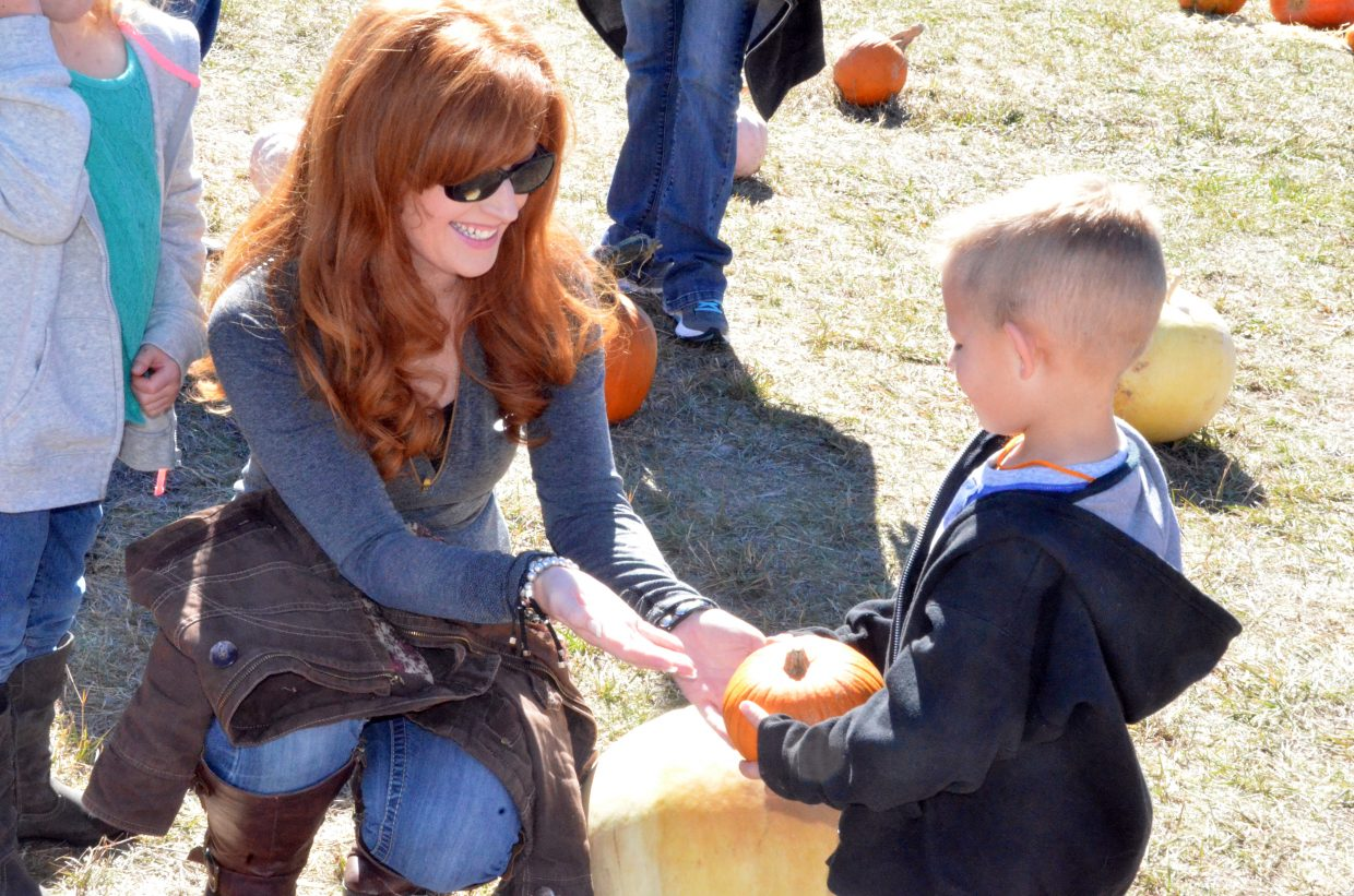 Shana Miles, helps son Brewer, 4, select a pumpkin at Saturday's pumpkin patch at Wyman Living History Museum.