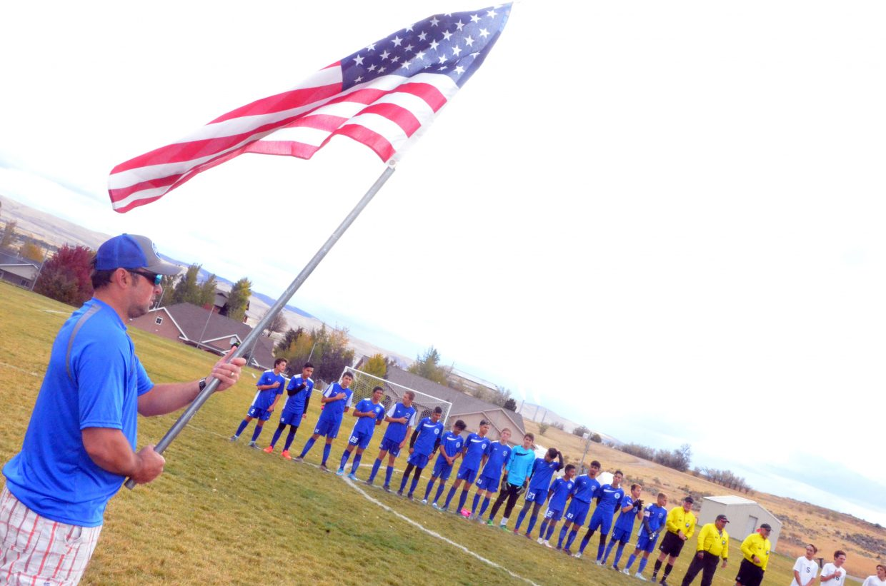 Moffat County High School assistant soccer coach Jeremy Chambers holds up the American flag for the national before MCHS boys soccer's Thursday game.