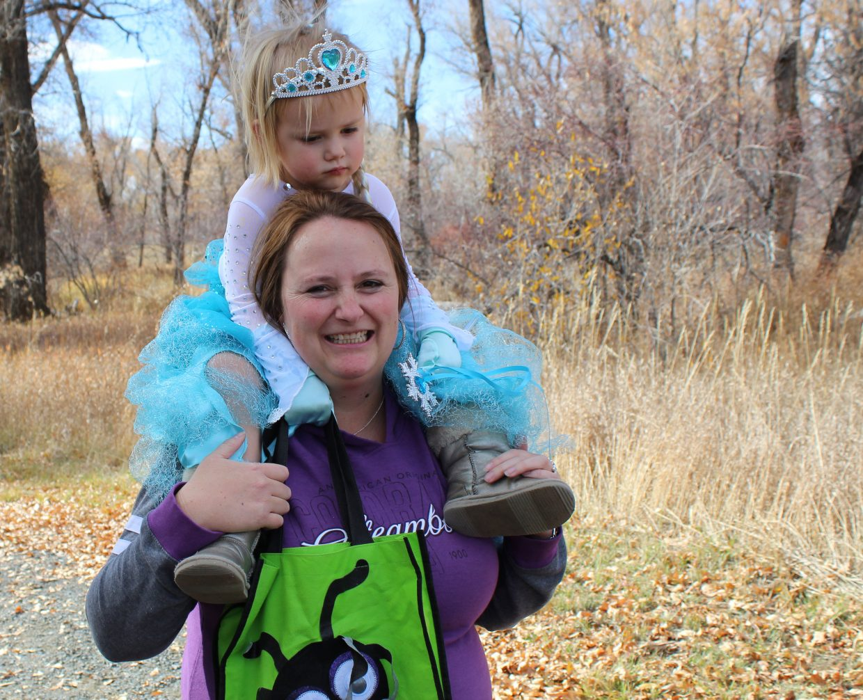 Kinsley Campbell, 2 1/2, gets a lift from her mom, Danielle Campbell, during this year's Hike or Treat event, held Saturday at Yampa River State Park.