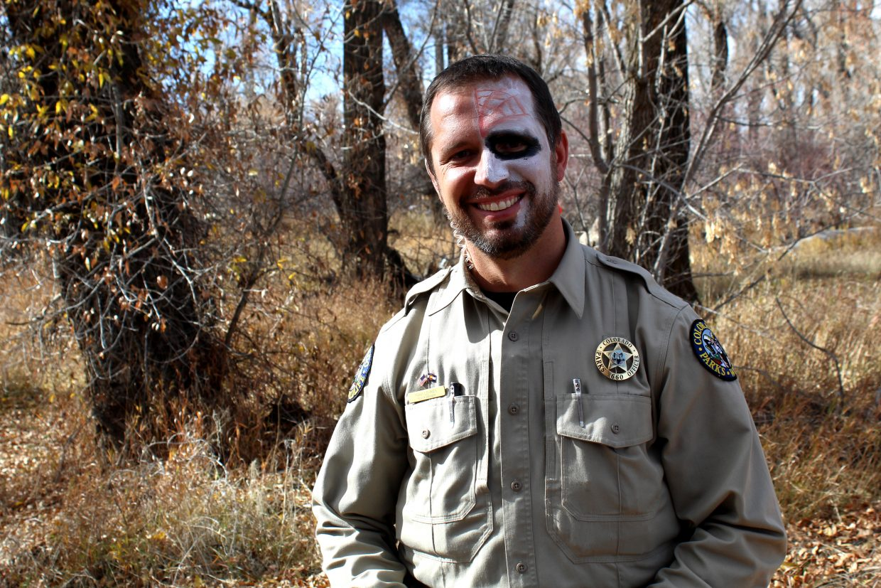Colorado Parks & Wildlife Officer Mark Lehman waits along the trail at Yampa River State Park on Saturday to hand out candy to kids during Saturday's Hike or Treat event. Lehman said the event began with 120 pounds of candy, which was