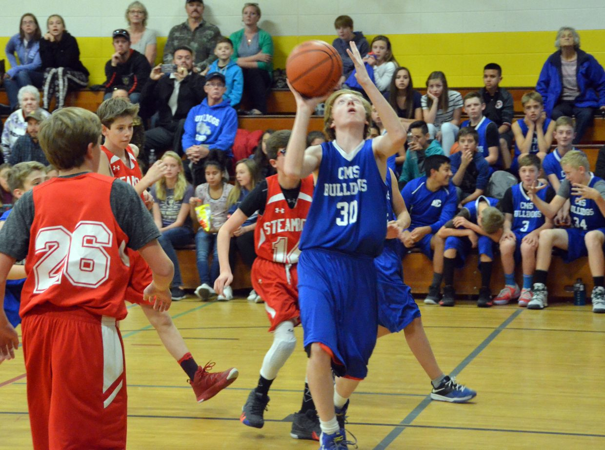 Craig Middle School's Jay Gates gets in close under the basket against Steamboat Springs.