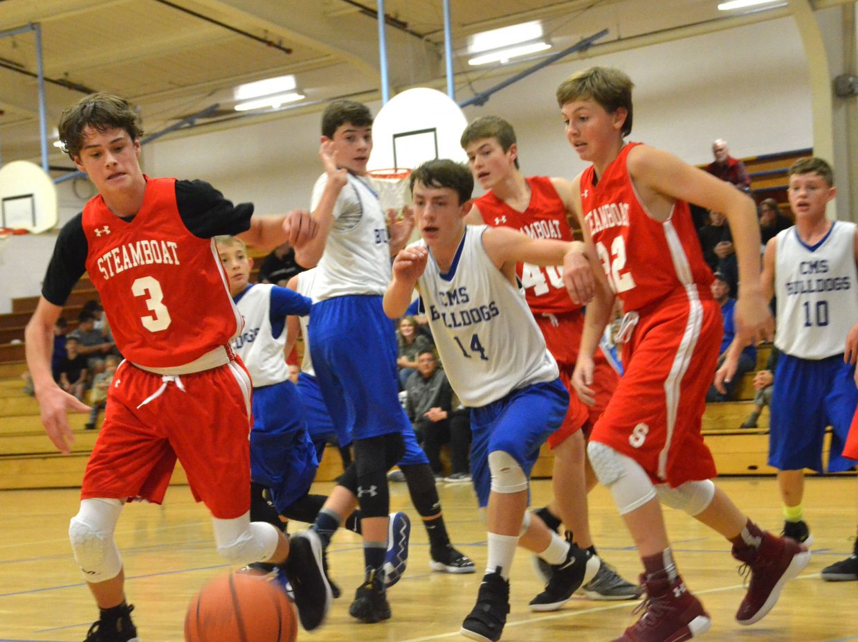 Craig Middle School basketball players chase after a loose against Steamboat Springs.