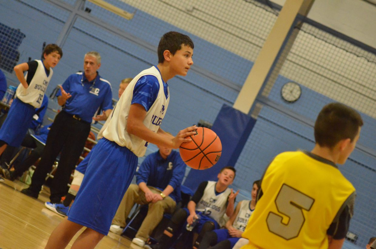 Craig Middle School's Johnny Lopez readies at the foul line as coach Steve Maneotis consults with teammates.