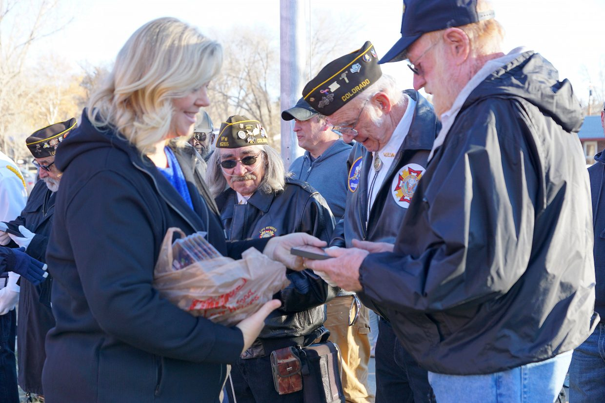 School Secretary Becky Fritz gives a small thank you gift from the school to each Veteran.