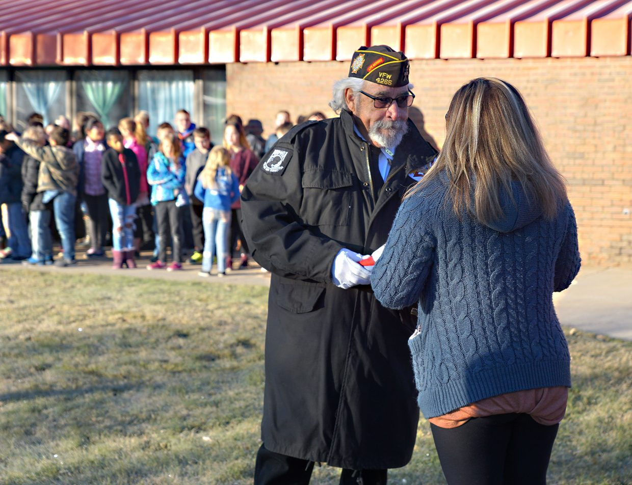 VFW Post Commander Johnny Garcia accepts the flag from Sunset teachers.