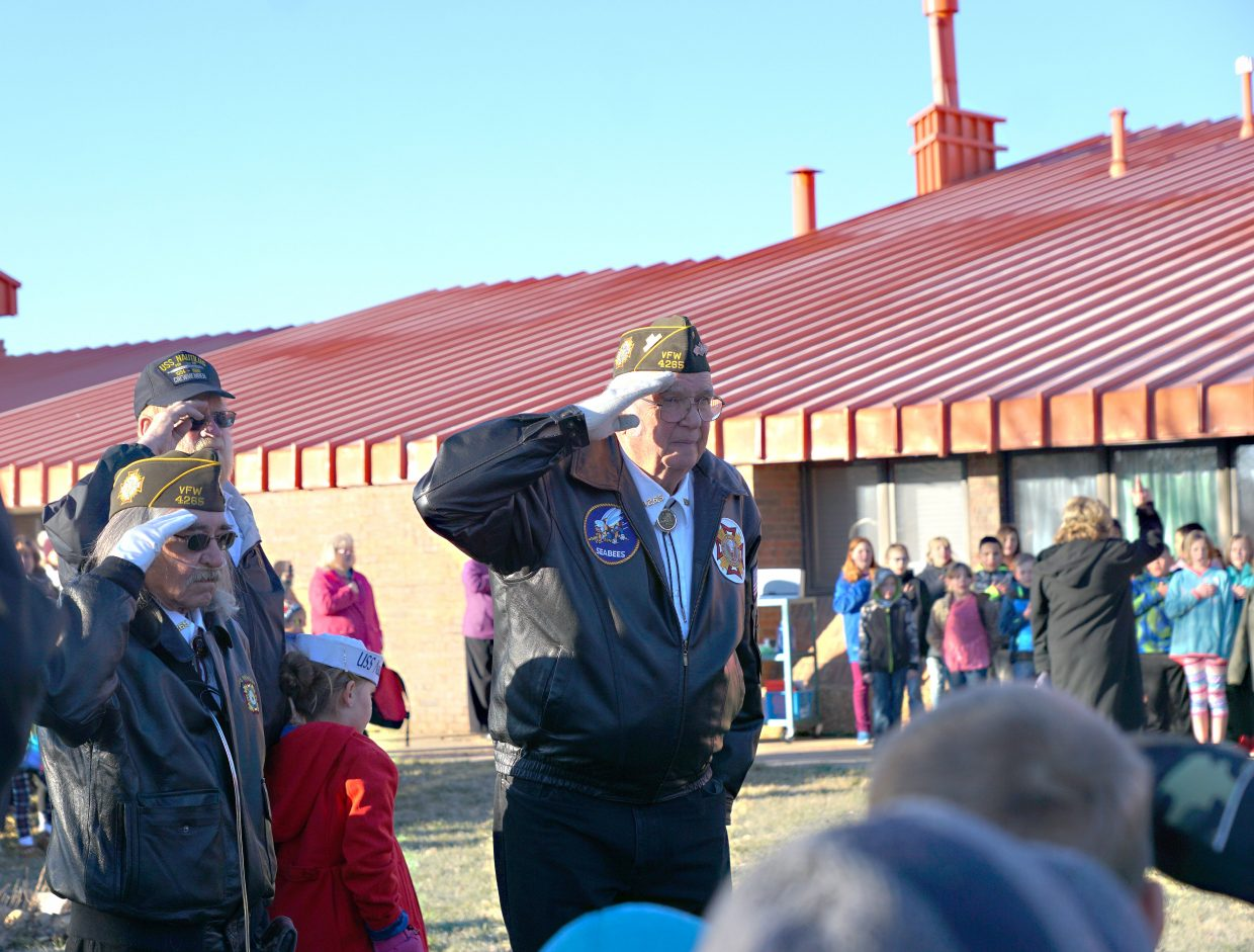 VFW Color Guard members salute the flag.