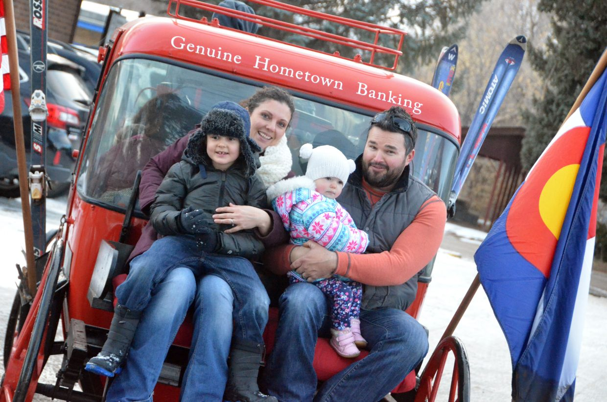The Dennison family hops on the back of the gondola pulled by horses during Down Home Christmas Saturday in Alice Pleasant Park.