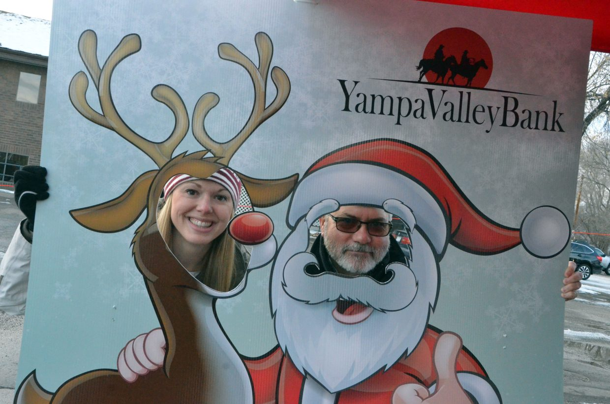 Ashley Kawcak and Dave Fleming peer through the holiday photo cut-out during Down Home Christmas Saturday in Alice Pleasant Park.