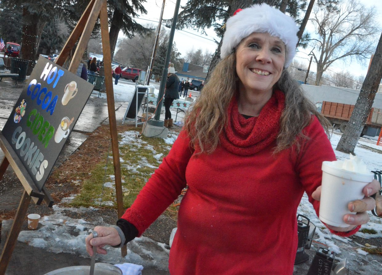 Downtown Business Association's Karen Brown offers up a cup of hot chocolate during Down Home Christmas Saturday in Alice Pleasant Park.