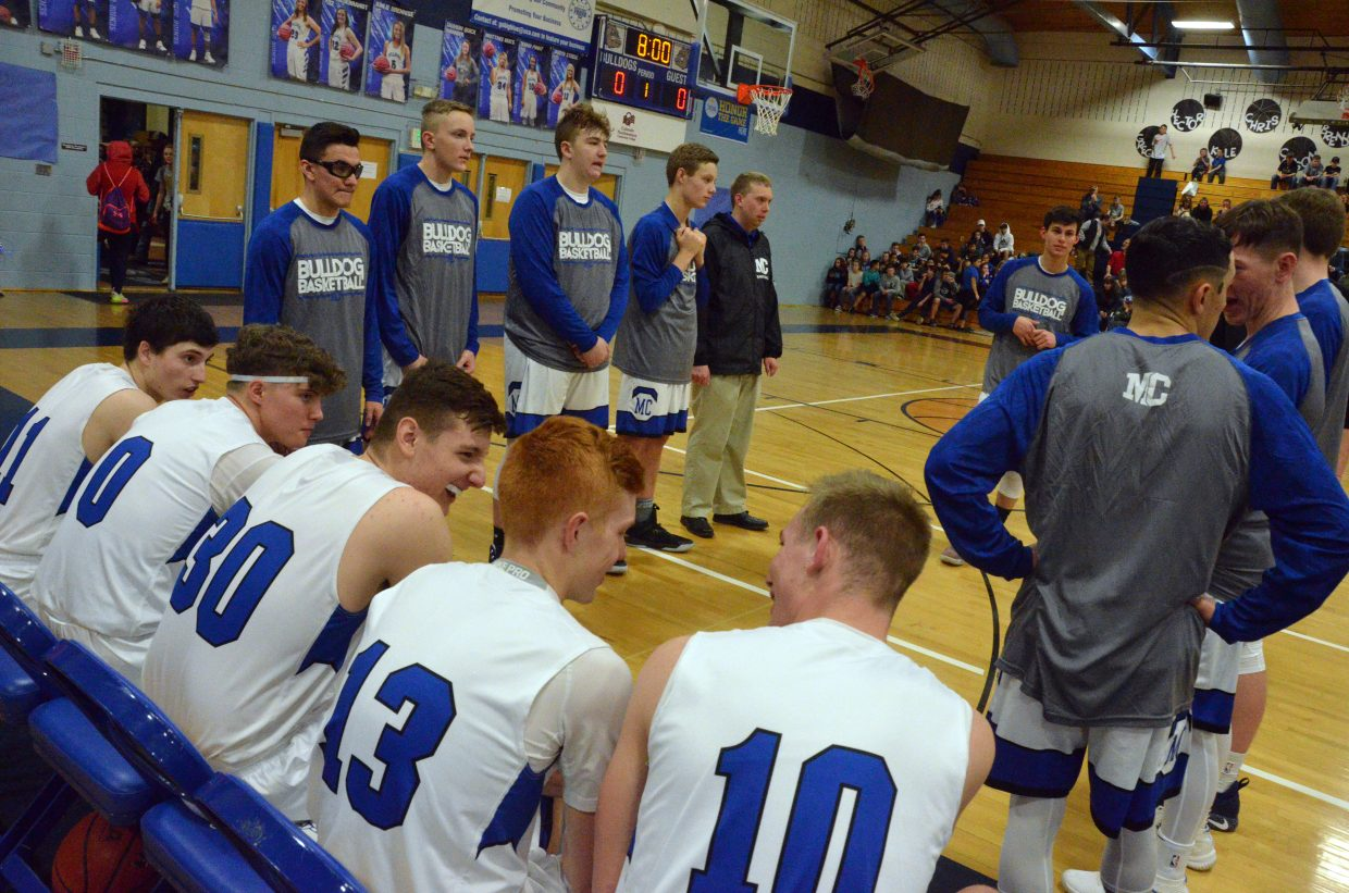Members of the Moffat County High School boys varsity basketball get pumped up before a game with Grand Valley.
