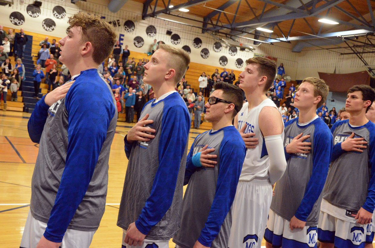 The Moffat County High School boys varsity basketball team observes the national anthem.