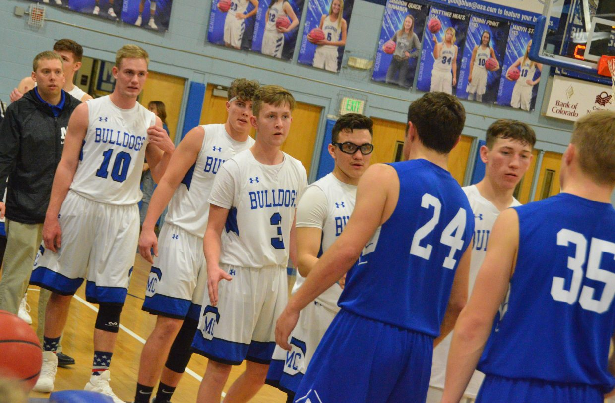 Moffat County High School varsity basketball players exchange congrats with opponents after a win over Cedaredge.