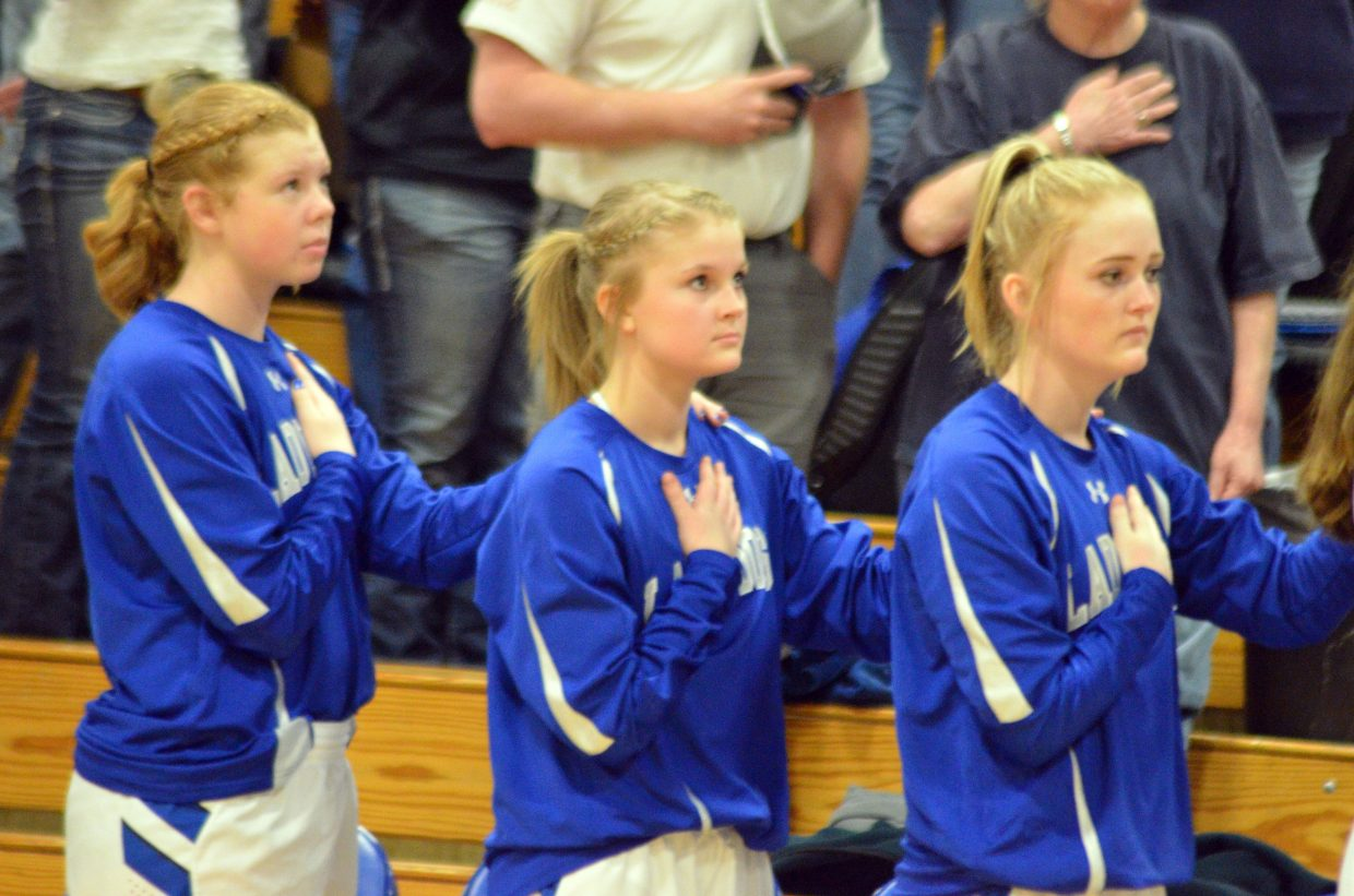 From left, Moffat County High School's Bree Meats, Jacie Evenson and Jaidyn Steele line up for the national anthem before the girls varsity basketball game.