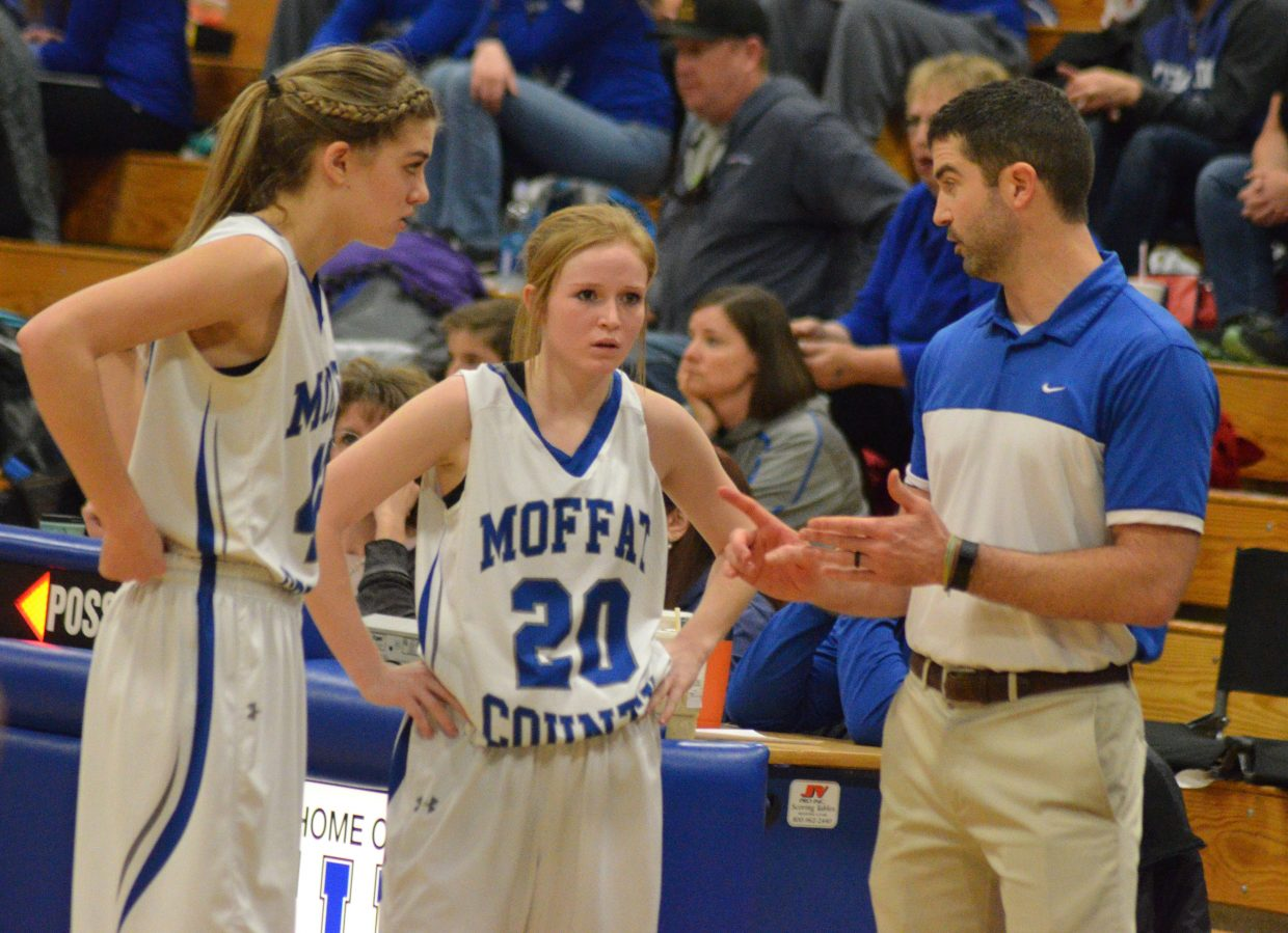 Moffat County High School's Rylie Felten, left and Reese Weber consult with girls JV basketball coach Joe Padon.