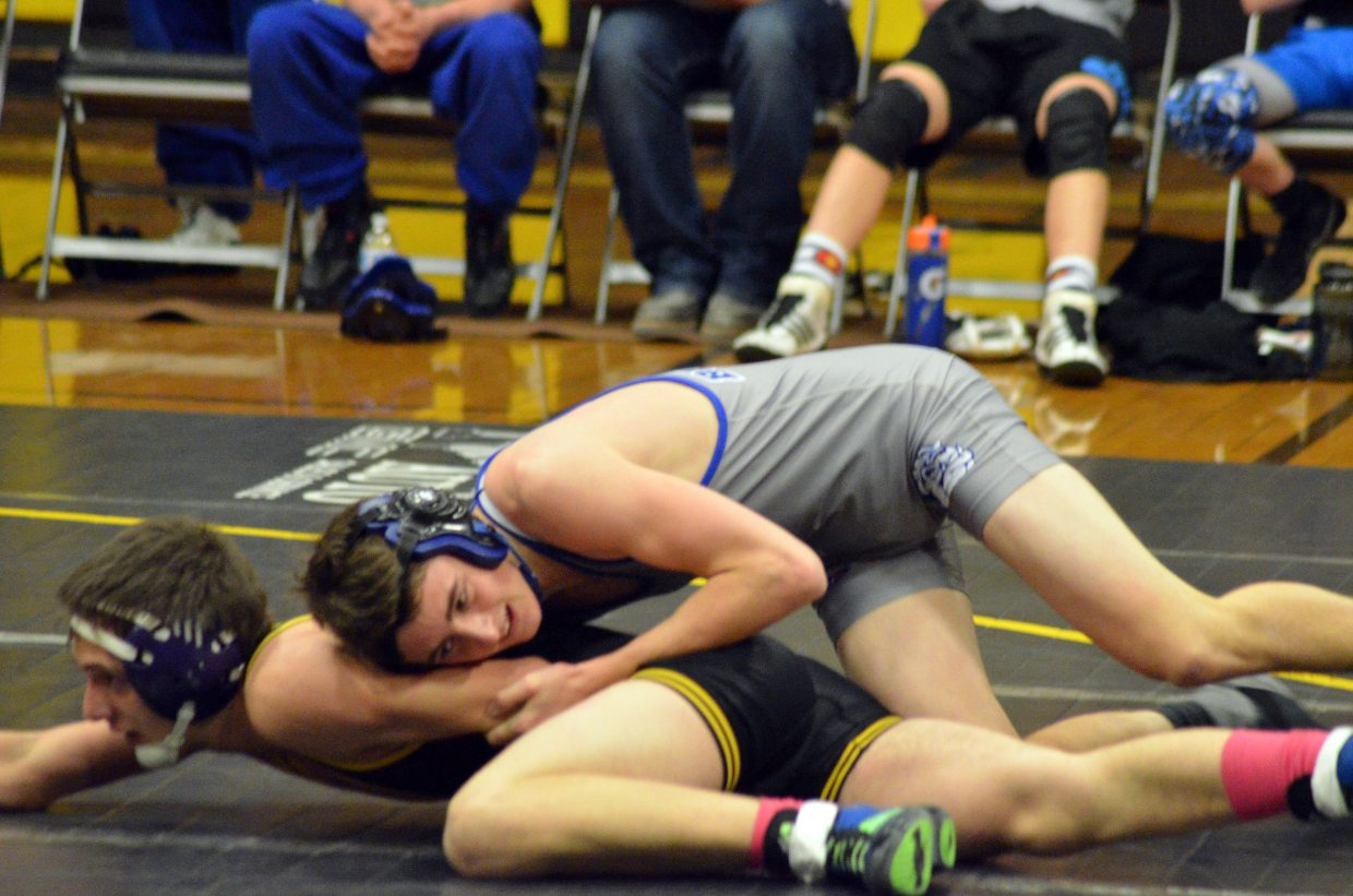 Moffat County High School's Blake Juergens drives Meeker's Dalton Portwood to the mat.