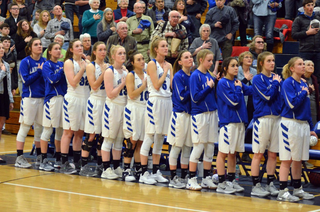 Members of the Moffat County High School girls basketball team observe the national anthem.