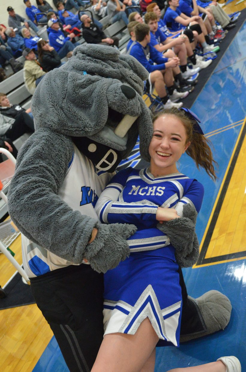 The Moffat County High School Bulldog mascot sweeps cheerleader Fiona Connor off her feet during a timeout in a Valentine's Day basketball game against Coal Ridge.