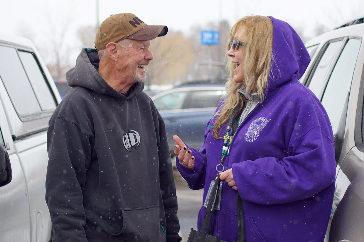 Retired from law enforcement, Rick Holford, left, shares a smile with dispatch supervisor Carlene Sanders during community outreach efforts Sunday, March 10.