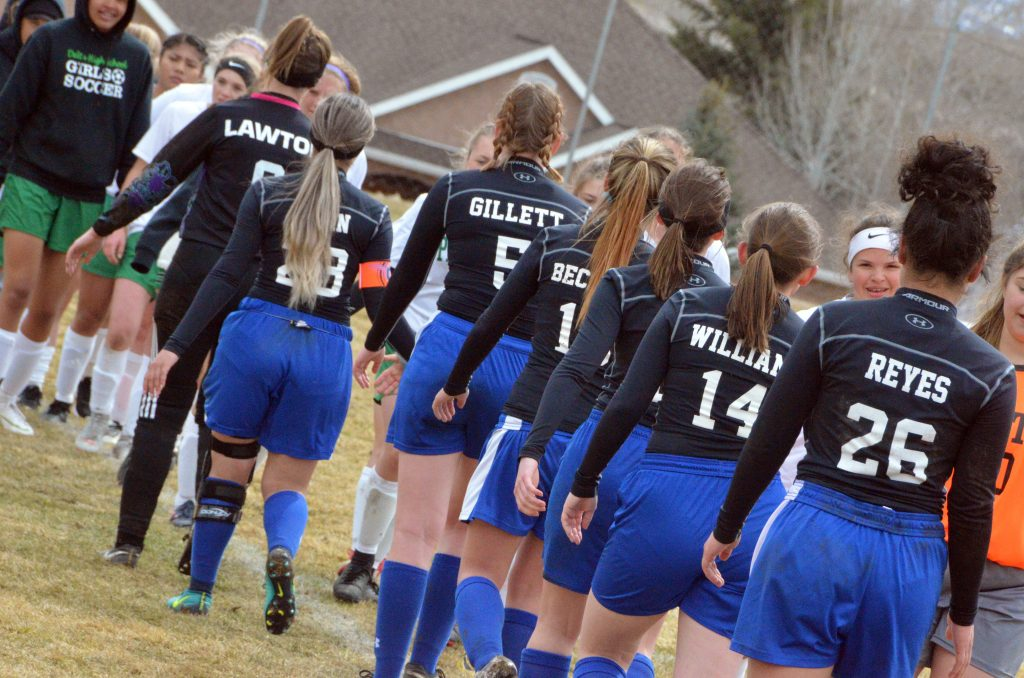Moffat County High School soccer shares high-fives following a game with Delta.