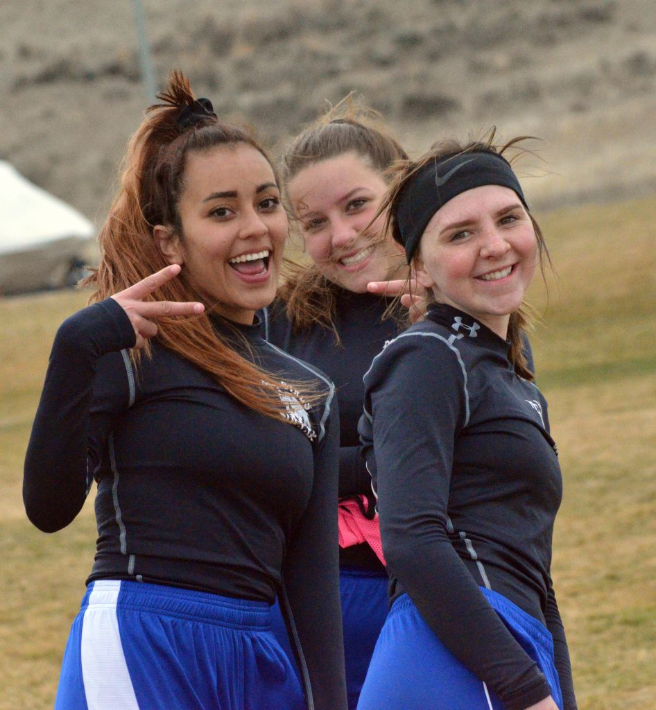 From left, Moffat County High School's Naomi Torres, Ebawnee Smercina and Tressa Otis kill time while waiting to sub in against Delta.