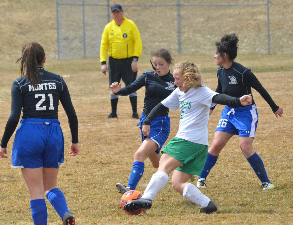 Moffat County High School soccer players swarm the Delta offense.