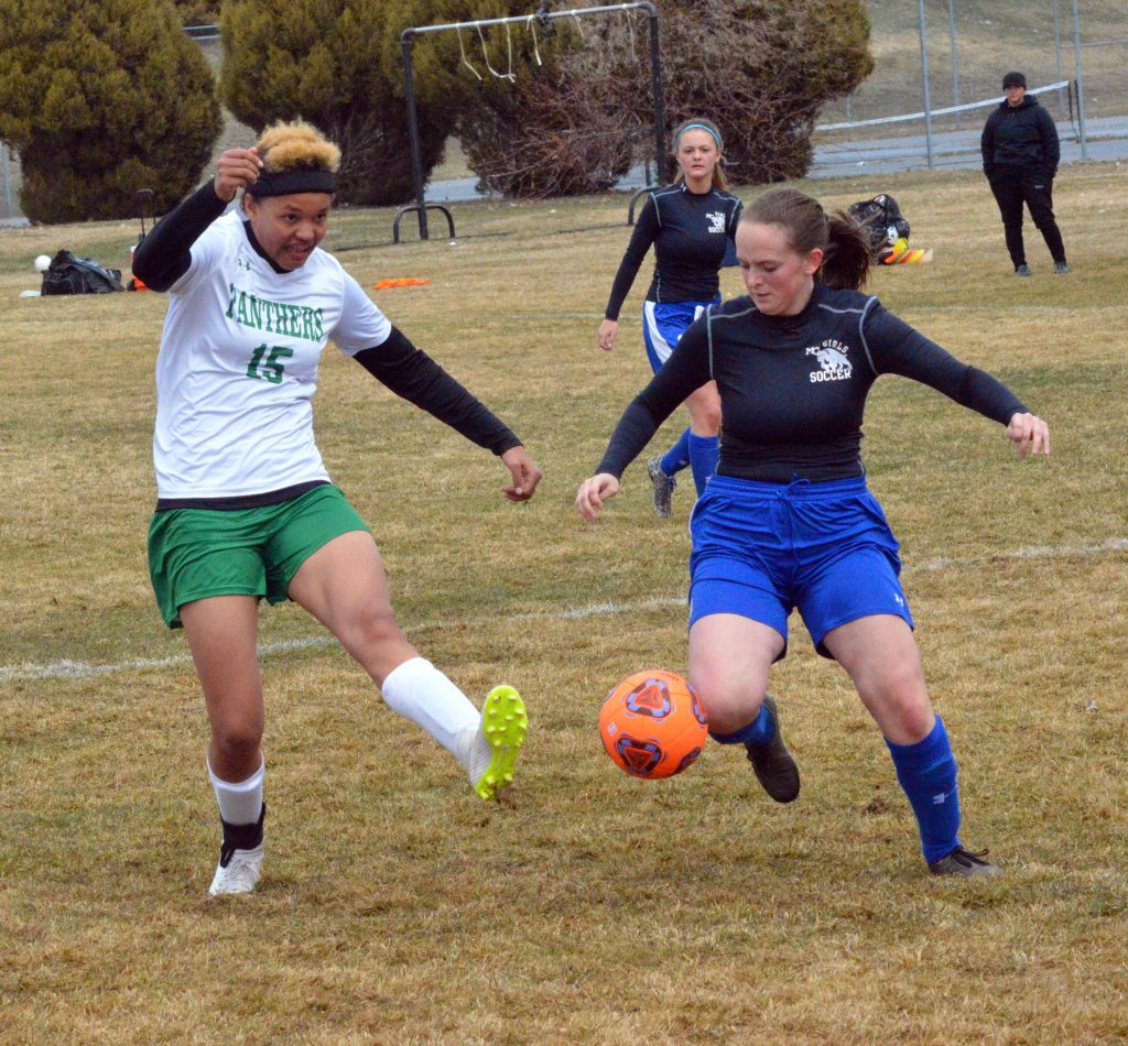 Moffat County High School's Brynlee Williams stays on top of Delta's Erika Kuta as she takes a shot on goal.