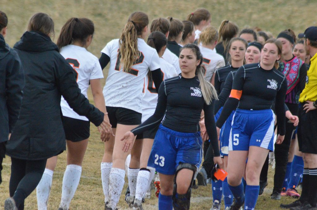 Moffat County High School soccer players share high-fives with Grand Junction.